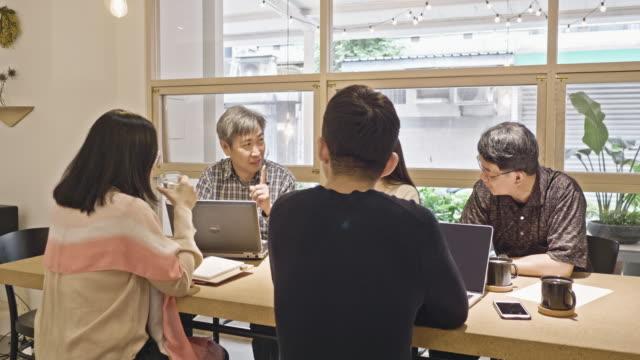 Asian Coworkers Brainstorming in Flex Office Space