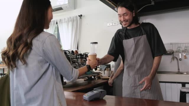 アジアの顧客はコーヒーを注文し、カフェのカウンターバーでクレジットカード機でスマートウォッチを支払う非接触nfcを使用します。 - クレジット決済点の映像素材/bロール