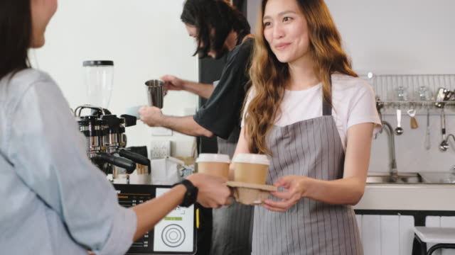 asian customer order coffee from tablet and use mobile phone pay contactless with tablet at counter bar in cafe.small business start up.customer service concept - giving stock videos & royalty-free footage