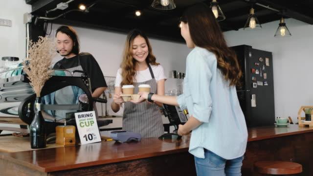 asiatische kunden bestellen kaffee vom tablet und verwenden handy zahlen kontaktlos mit tablet an der theke bar in café.small business start up.customer servicekonzept - kiosk stock-videos und b-roll-filmmaterial