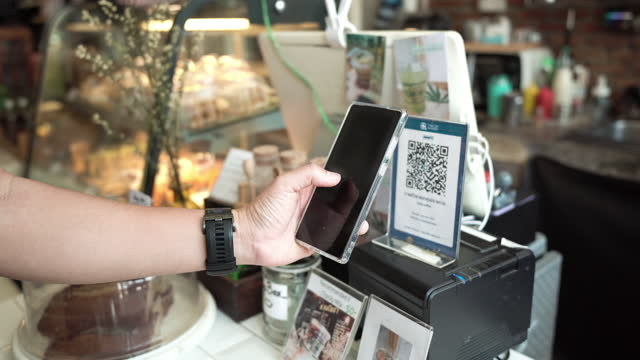 asian customer use mobile phone pay contactless at counter bar in cafe. - customer stock videos & royalty-free footage
