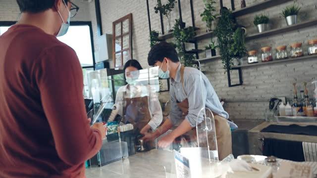 アジアの顧客は、並んで立って、カフェでコーヒーを拾って待っている保護マスクを身に着けています - アシスタント点の映像素材/bロール