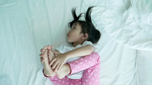 Asian cute baby girl trying stretching her leg while open her leg with positive emotion