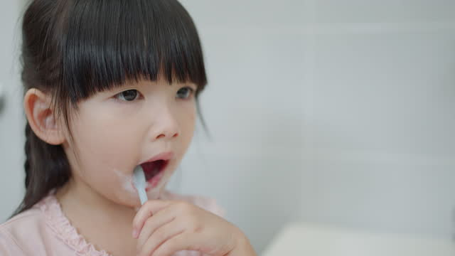 asian cute child girl or kid brushing her teeth by toothbrush in the bathroom. dental hygiene healthcare concept. - brushing stock videos & royalty-free footage