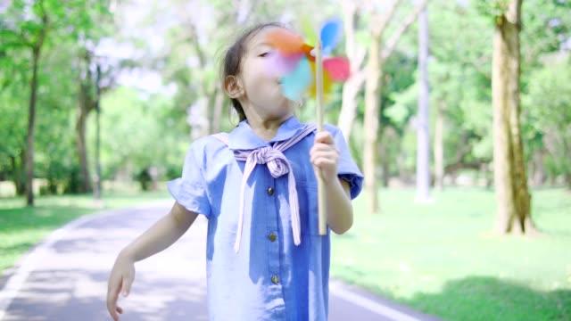 asiatisk söt tjej blåser färgglada fläkt i parken. - korta ärmar bildbanksvideor och videomaterial från bakom kulisserna