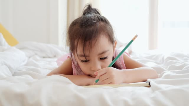 asian cute girl drawing and writing in the bed room. - quaderno video stock e b–roll