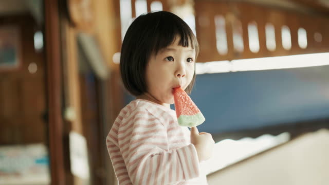 asian cute girl is eating ice-cream with watermelon shape with positive emotion with relax and enjoy eating - snack stock videos and b-roll footage