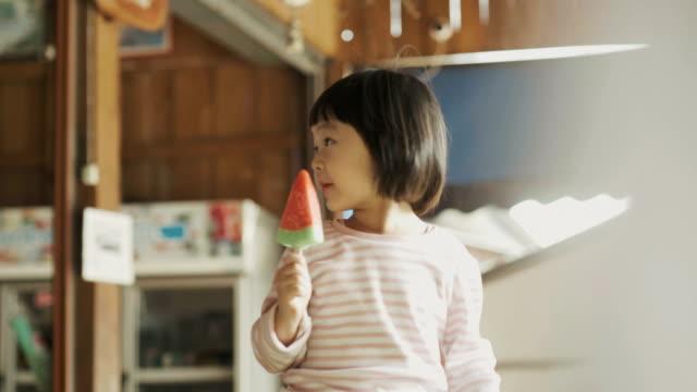 süße asiatin ist essen ein eis mit wassermelone form mit positiven emotionen mit entspannung und genuss - eis stock-videos und b-roll-filmmaterial