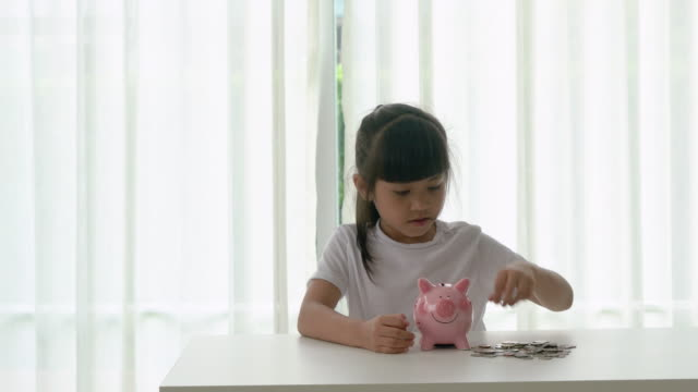 vidéos et rushes de fille mignonne asiatique économisant l'argent mettant des pièces dans la tirelire sur la table à la maison. - tirelire