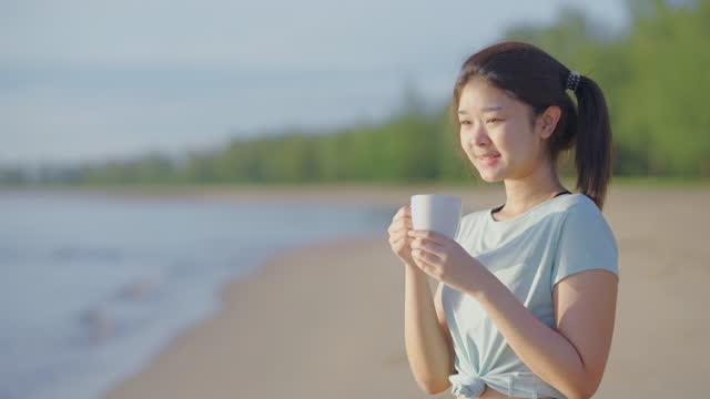 asian cute girl she was drinking milk in the morning at the beach. - dairy product bildbanksvideor och videomaterial från bakom kulisserna
