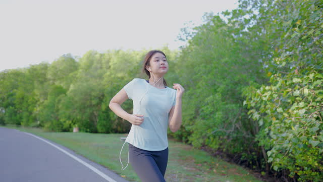 asian cute girl she was jogging in the morning in the garden and the sun was shining, 4k resolution. - headphones stock videos & royalty-free footage