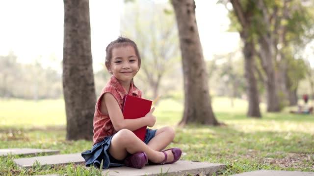公共の公園で描くアジアのかわいい女の子。教育の概念。 - 学校備品点の映像素材/bロール