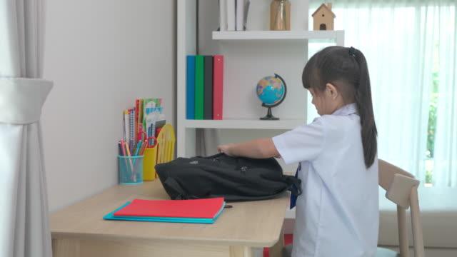 vidéos et rushes de filles asiatiques mignonnes d'école primaire faisant leurs valises d'école, préparant pour le premier jour d'école. la routine de l'école du matin pour la journée dans la vie se préparant pour l'école. - cartable
