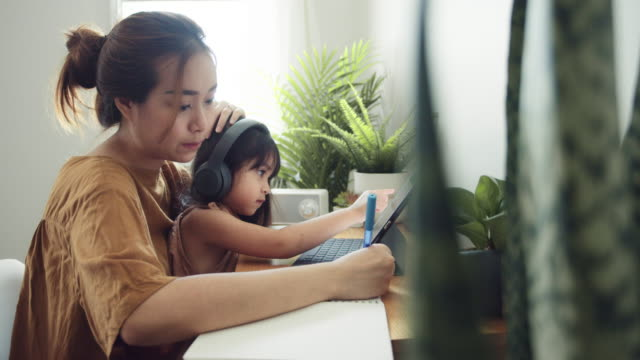 asian daughter attending to online class from home with mother. - asian stock videos & royalty-free footage