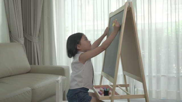 asian daughter sum mathematics with color chalk in blackboard at table in living room at home. back to school and education concept. - addition key stock videos & royalty-free footage