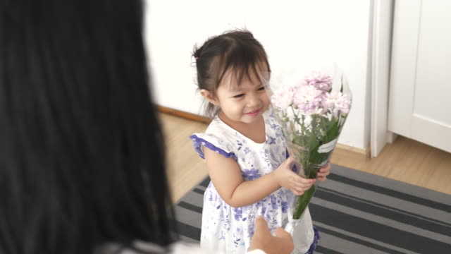 asian daughter surprising mother with violet flowers on mother's day - stock video - receiving stock videos & royalty-free footage