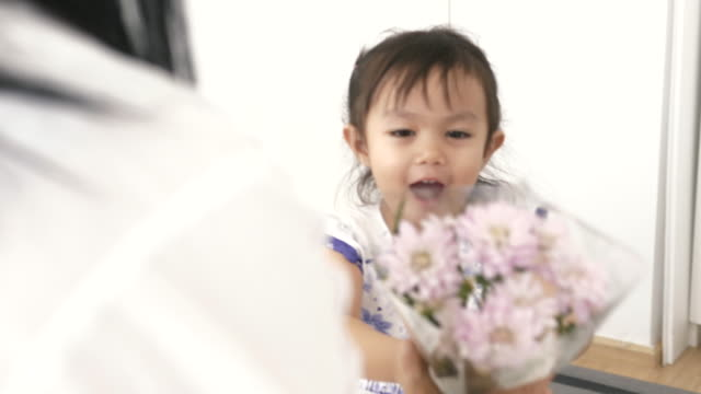 Asian Daughter surprising mother with violet flowers on Mother's Day - Stock video