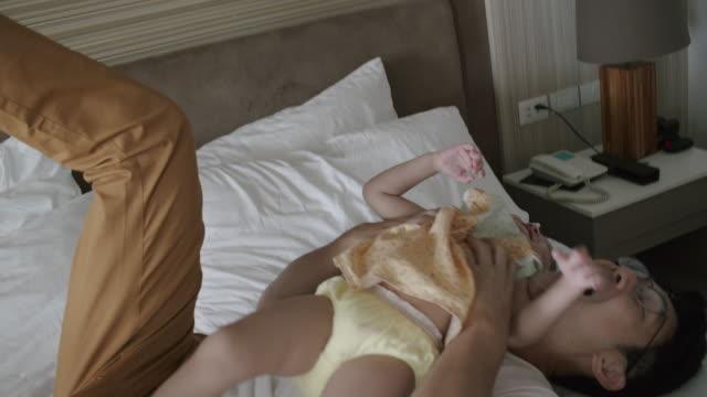 figlia asiatica che gioca con il padre a letto. padre che abbraccia o abbraccia la sua simpatica bambina a casa. - single father video stock e b–roll