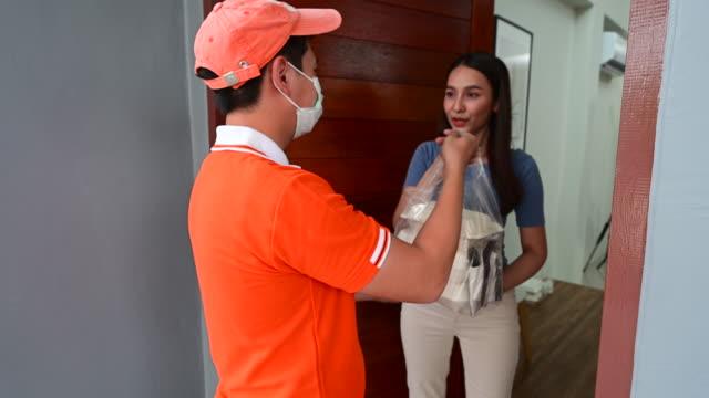 asiatische liefern mann trägt gesichtsmaske in orange einheitliche handhabung tasche von lebensmitteln geben, um weibliche kunden vor dem haus. liefermann und express-lebensmittel-lieferservice während covid19. - papiertüte stock-videos und b-roll-filmmaterial