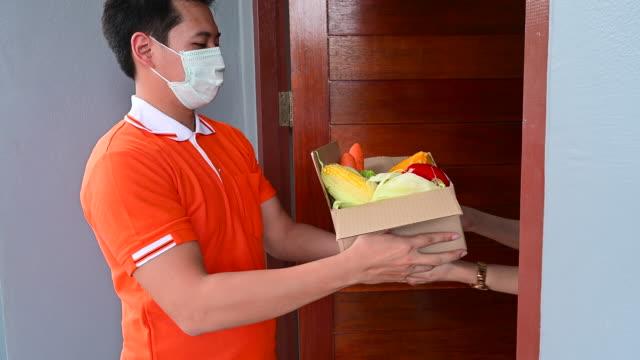 vidéos et rushes de asiatique livrer l'homme portant le masque de visage dans la boîte de manipulation d'uniforme orange de nourriture, fruit, légume donnent au client féminin devant la maison. facteur et service de livraison express d'épicerie pendant covide19. - sachet en papier