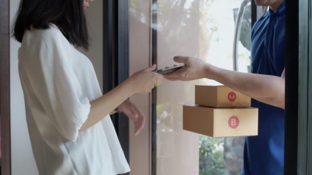 女性のお客様に紙の小包箱の配達を運ぶアジアの配達員。郵便配達サービスのコンセプト。4k uhdのスローモーション。 - 小荷物点の映像素材/bロール