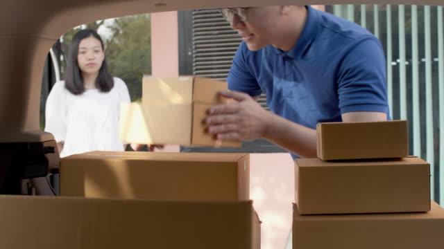 vídeos y material grabado en eventos de stock de el repartidor asiático comprueba y lleva cajas de paquetes de papel en la parte trasera del coche de entrega antes de la entrega a las mujeres clientes. concepto de entrega postal service.4k uhd. - enviar actividad