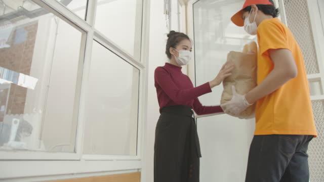 コロナウイルス検疫中にアジアの女性顧客に食料品を配達するアジアの配達員 - 買い物袋点の映像素材/bロール