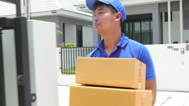 vídeos y material grabado en eventos de stock de los concejales asiáticos llevan un uniforme azul con una gorra azul y máscara facial manipulando cajas de cartón para regalar al cliente femenino frente a la casa. compras en línea y entrega exprés - poste de madera