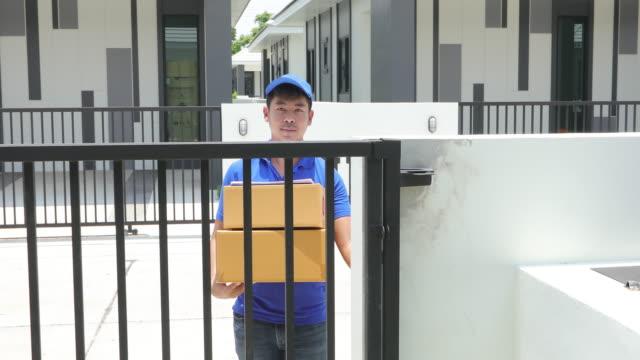 青い帽子とフェイスマスクで青い制服を着たアジアの配達員は、家の前で女性の顧客に与えるために段ボール箱を扱います。オンラインショッピングとエクスプレス配信 - 配達員点の映像素材/bロール