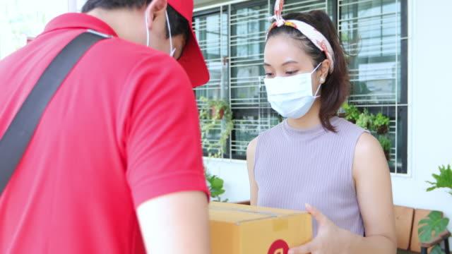 vídeos y material grabado en eventos de stock de los militares asiáticos que llevan un uniforme rojo con una gorra roja y una máscara facial que manipulan cajas de cartón para dar a la clienta frente a la casa. compras en línea y entrega exprés - poste de madera