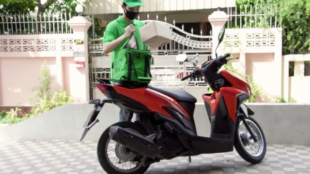vídeos de stock, filmes e b-roll de equipe de entrega asiática. - motocicleta