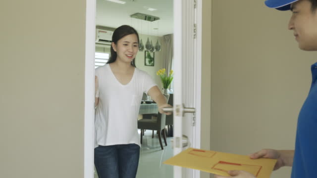 asian delivery young man in blue uniform smile and holding letter or document envelope in front house and asian woman accepting a delivery of envelope from deliveryman. advertising, business, transportation concept. - envelope stock videos & royalty-free footage