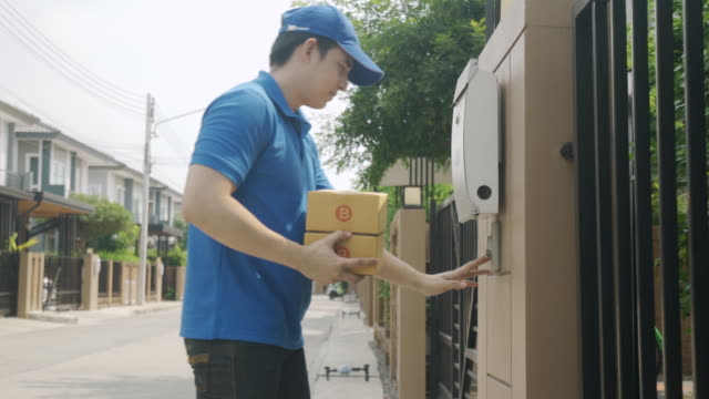 vídeos de stock e filmes b-roll de asian delivery young man in blue uniform smile and holding pile of cardboard boxes in front house village with copy space. advertising, business, transportation concept. - tocar