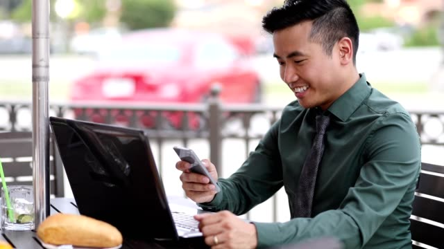 asian descent business man working at outdoor cafe. - professional occupation stock videos & royalty-free footage