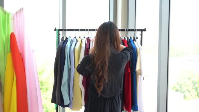 asiatische designerin sucht neue kleidung - maßkonfektion stock-videos und b-roll-filmmaterial