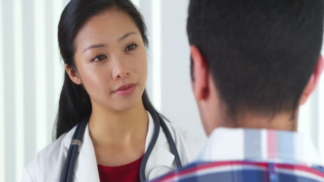 vídeos y material grabado en eventos de stock de asian doctor answering questions from patient - fiabilidad