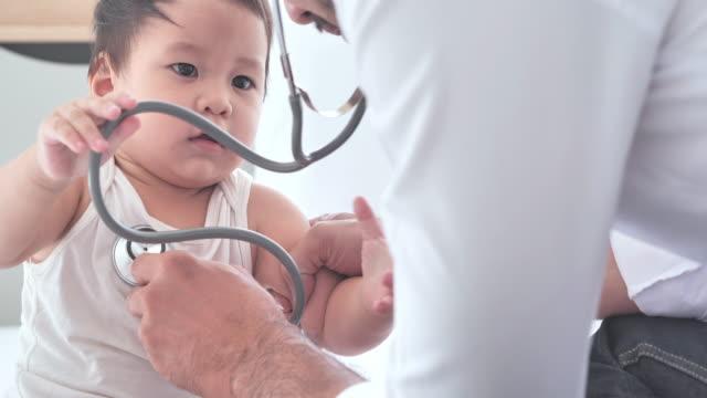 アジアの医師は、コロナウイルスまたはcovid-19.乳児を調べる専門の小児科医の男性に流行病を防ぐためにアジアの男の子に心臓をチェックします。医師と患者の相談 - 小児科医点の映像素材/bロール