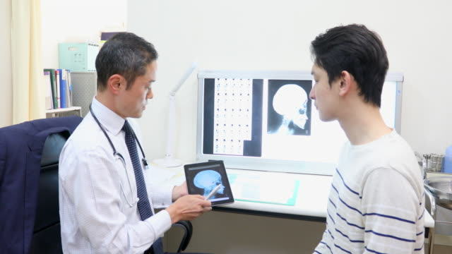 asian doctor examining an x-ray with a patient - medical examination room stock videos & royalty-free footage