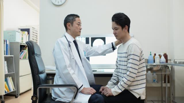 Aziatische arts onderzoekt de nek van de patiënt