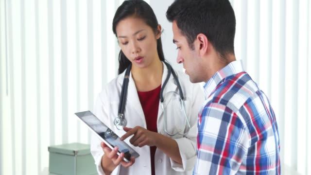 asian doctor explaining neck xray to patient - menschliches gelenk stock-videos und b-roll-filmmaterial