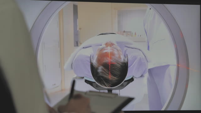 asian doctor female with health care staff observe in a scanning room in a new modern treatment hospital by senior men patient is scanned by mri, ct scanner procedure.magnetic resonance examination. - tomography stock videos & royalty-free footage