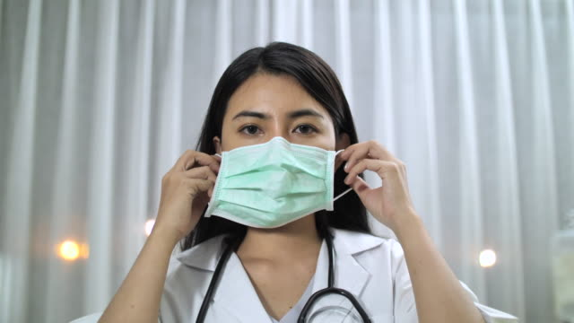 asian doctor putting on surgical mask - getting dressed stock videos & royalty-free footage