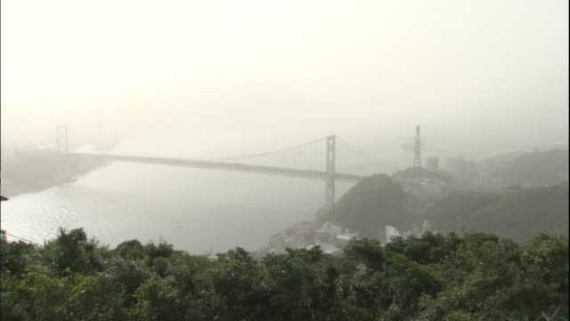 asian dust covers the kanmon bridge and the kanmon straits in shimonoseki, japan. - straits stock videos and b-roll footage