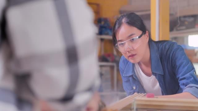vidéos et rushes de les hommes âgés asiatiques charpentier enseignant la fille d'adolescent avec la planche en bois à l'atelier. éducation, leadership, famille, personnes, petite entreprise, leadership, vision, retraite, innovation, opportunité, femmes en stem, conce - apprenti