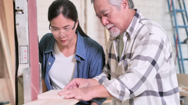 asian elderly men carpenter teaching teenager girl with wood plank at workshop.education, leadership, family, people, small business, leadership, vision, retirement, innovation, opportunity, women in stem, blue collar workers concept - chinese ethnicity stock videos & royalty-free footage