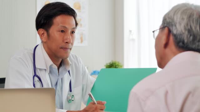vídeos de stock, filmes e b-roll de idosos asiáticos que conversam com jovens médicos do sexo masculino ajudam paciente em consulta médica para prevenir epidemias de coronavirus ou covid-19 no hospital. idosos, médicos,cuidadores,cuidados, aposentadoria, educção, conceito de voluntaria - exame médico equipamento médico