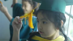 Asian elementary age girls wearing graduation caps and gowns smile while standing inside school.