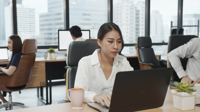 4k uhd : asian employee officer woman working on laptop with modern office background. - small office stock videos & royalty-free footage