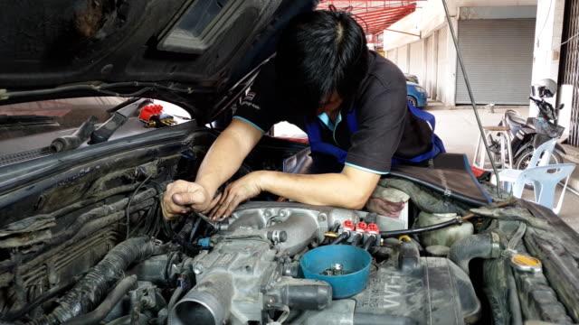 アジアのエンジンメカニックがエンジンを修理しています。 - 作業場点の映像素材/bロール