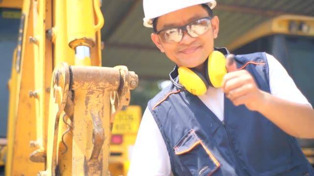 vídeos de stock, filmes e b-roll de o engenheiro asiático check examina um esquema de uma escavadeira, câmera lenta. - trabalhador manual